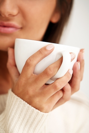 White cup in beautiful brunette woman hands photo