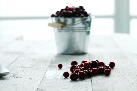 Fresh cranberries in a silver bucket on a white wooden table photo