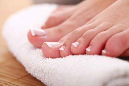 french pedicure: Beautiful foot with french pedicure on white towel Stock Photo