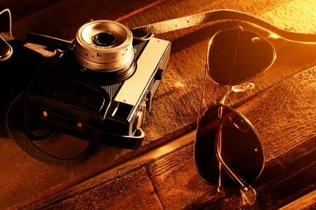 photocamera: Eyeglasses with retro photocamera over wooden surface