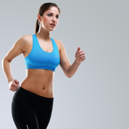 Young beautiful woman in fitness wear isolated over background Stock Photo - 17975294