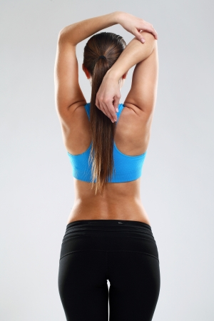 Young woman in fitness wear isolated over background photo