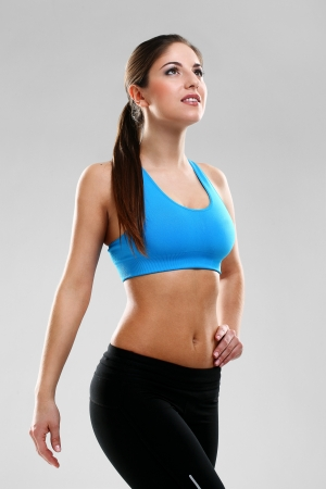 Young beautiful woman in fitness wear isolated over background