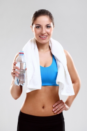 Young woman in fitness wear with towel isolated over background photo