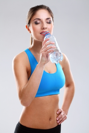 Young woman in fitness wear drinking iolated over white background photo