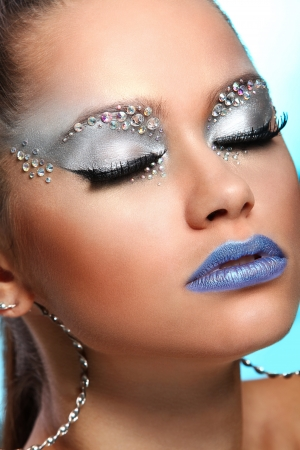Portrait of woman with artistic make-up and rhinestones over background photo