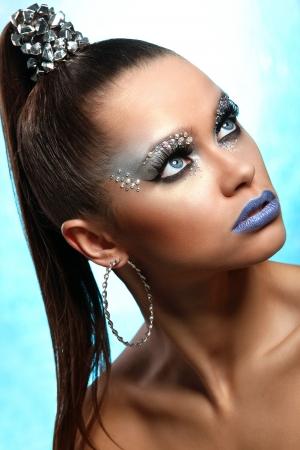 fantasy makeup: Retrato de mujer con maquillaje artístico y pedrería sobre fondo