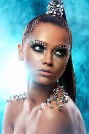 Portrait de femme avec maquillage artistique et strass sur fond