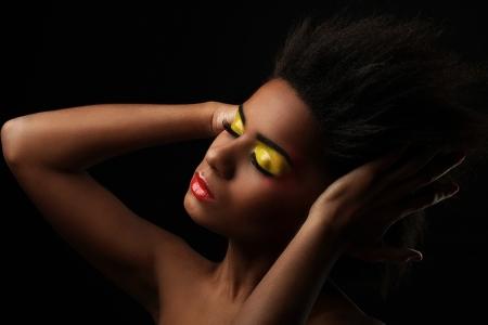 mannequin africain: Belle femme noire avec maquillage brillant isol� sur fond noir Banque d'images