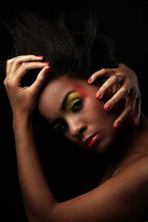 maquillaje de fantasia: Mujer hermosa con maquillaje negro brillante aislado sobre fondo negro
