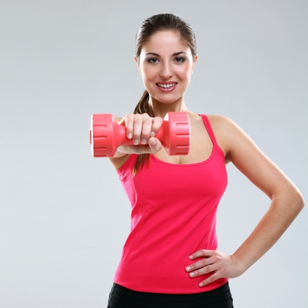 Young beautiful woman in fitness wear with dumbbells isolated over background