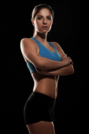 Young beautiful woman in fitness wear isolated over black background photo