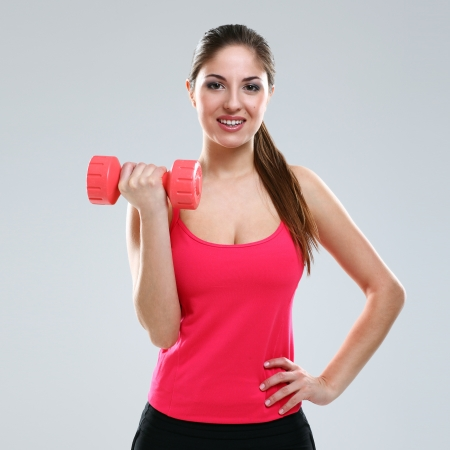 Young beautiful woman in fitness wear with dumbbells isolated over background photo