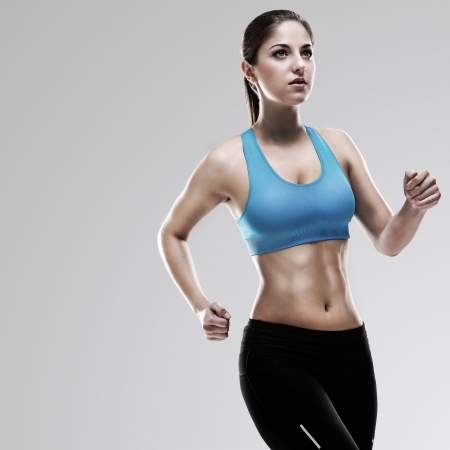 Young beautiful woman in fitness wear runs isolated over background photo