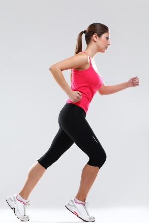 krachtige vrouw: Jonge mooie vrouw in fitness slijtage loopt die over achtergrond Stockfoto