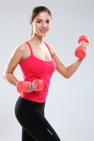 Young beautiful woman in fitness wear with dumbbells isolated over background Stock Photo - 18137368