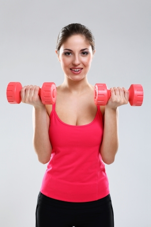Young beautiful woman in fitness wear with dumbbells isolated over background Stock Photo - 18137460