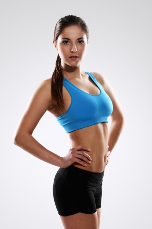 Young beautiful woman in fitness wear isolated over white background photo