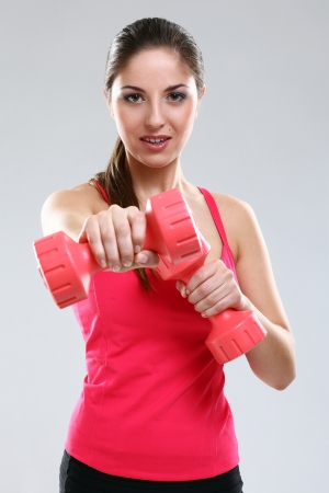Young beautiful woman in fitness wear isolated over background photo