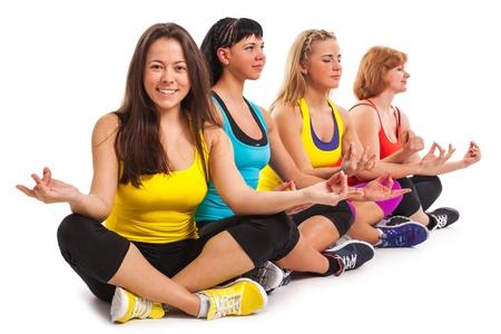 Group of women enjoying yoga over white background photo
