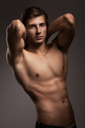 hombre desnudo: Apuesto joven con el torso desnudo sobre un fondo gris