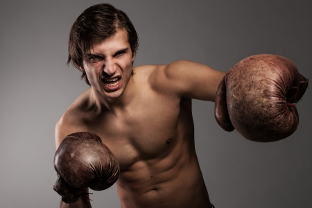 Agressive guy in a boxing gloves ready for a fight photo