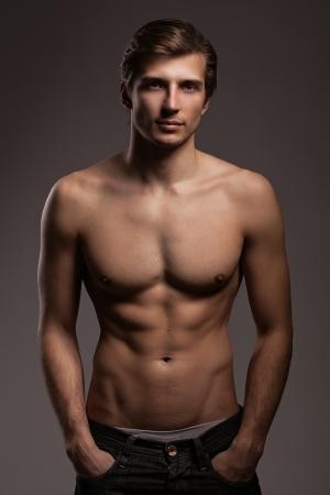homme nu: Beau jeune homme au torse nu sur un fond gris