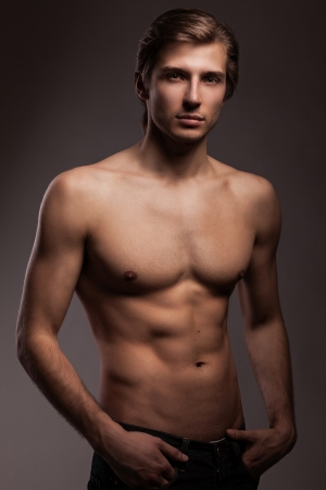 Handsome young man with naked torso on a grey background photo