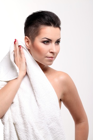 short haircut: Young woman with short haircut in towel isolated over white background