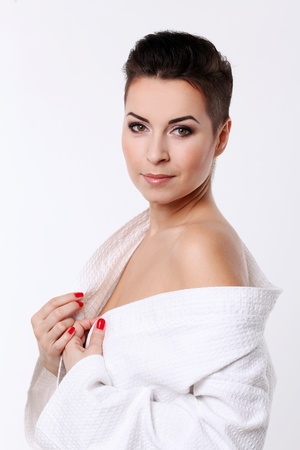 short haircut: Young woman with short haircut in bathrobe isolated over white background