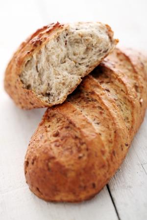 буханка: Домашний хлеб хрустящий с зернами на белом деревянном столе