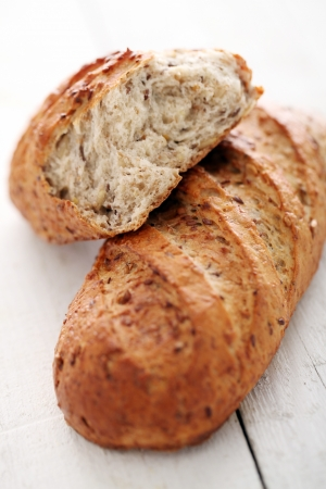 italian bread: Homemade crunchy bread with grains on a white wooden table