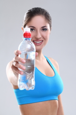 Beautiful caucasian woman with water in fitness wear over background photo