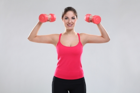 Beautiful caucasian woman in fitness wear with dumbbells over background Stock Photo - 19165090