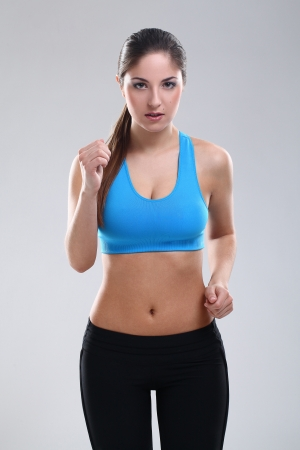 Beautiful caucasian woman in fitness wear over background photo