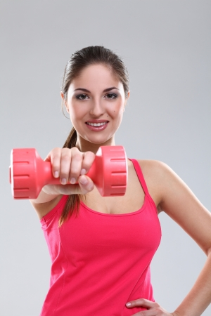 Beautiful caucasian woman in fitness wear with dumbbells over background photo