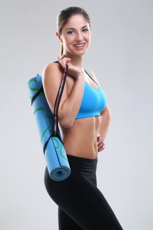 Beautiful caucasian woman in fitness wear with yoga mat over background photo