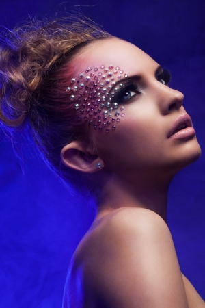 fantasy makeup: Beautiful woman with fantasy makeup on a blue background