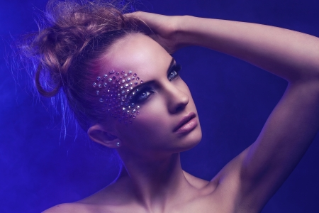 Beautiful woman with fantasy makeup on a blue background photo