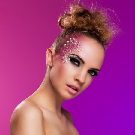 Beautiful woman with fantasy makeup on a violet background photo