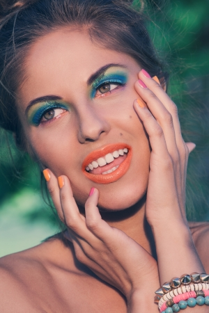 A portrait of a girl posing with beautiful artistic makeup and colorful handmade bracelets photo