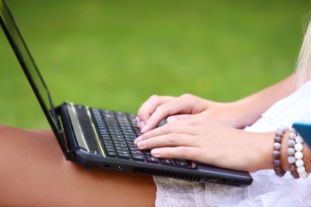 A closeup picture of a laptop in womans hands at a park photo