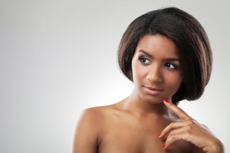 mujeres negras desnudas: A close up retrato de una bella mujer de piel oscura está tocando su hombro desnudo