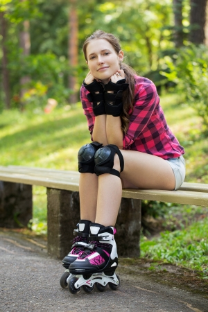 A portrait of a girl with rollerblades, who is sitting on a branch in a park photo