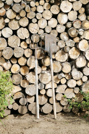 A large wall of timber with a rake and a shovel near it photo