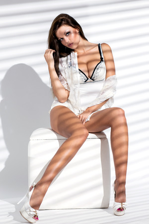 Elegant woman in lingerie is posing while sitting on a sofa chair and spreading her legs photo