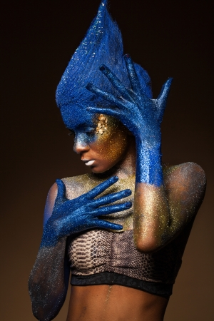 body paint sexy: Portrait of a woman who is posing covered with blue and gold paint
