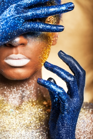 Portrait of a woman who is posing covered with blue and gold paint