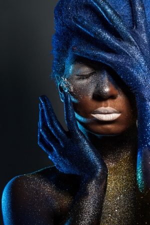 Portrait of a woman who is posing covered with blue and gold paint photo