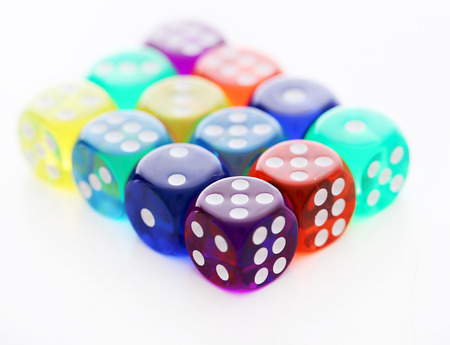 Many colorful dice are lying together over a white background photo